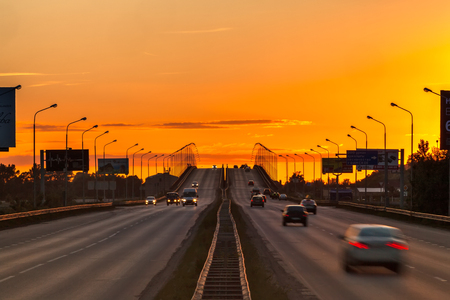 Symmetrical overpass extending beyond the horizon in the yellow orange light of the setting sun at the sunset.