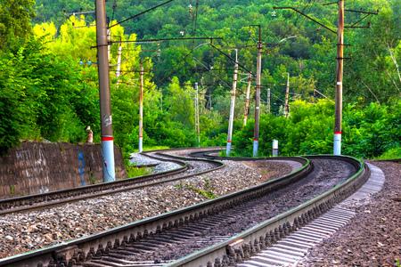 Schienen und Schwellen einer doppelt gewundenen Bahnstrecke in einem grünen Wald zwischen schiefen, schiefen Säulenpfosten. Standard-Bild