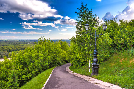 Footpath around the monument in the shade of green trees with lush foliage and a cast-iron black street lamp against a blue sky with white clouds.