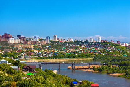 White River in the city center on the background of private houses with colorful roofs on a slope with green trees and modern high-rise buildings.