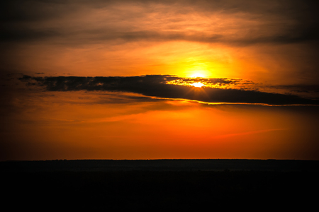 Cloud silhouette on a bright colorful orange sky hiding the yellow sun over the black steppe plain.