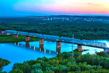 Railway bridge is reflected over the calm White River, surrounded by a green lush forest on the outskirts of the city under the evening blue sky at dusk.