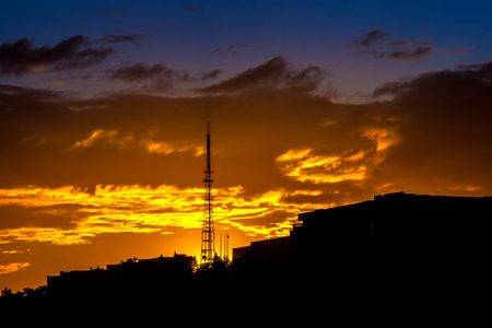 Silhouette of a television tower on the background of dramatic beautiful orange clouds on a yellow blue dark sky during sunset. 版權商用圖片