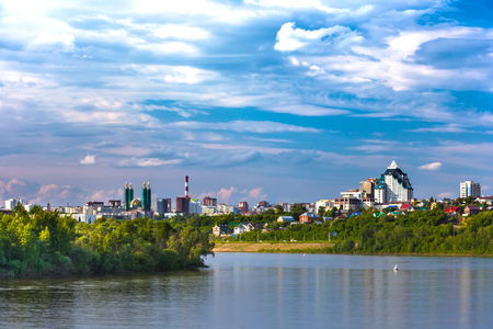 Belaya river bank, overgrown with lush shrubs and green trees under colorful white clouds against the blue sky against the background of urban buildings in the distance. 写真素材