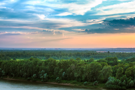 Dense green forest on the banks of the river view from above at dusk with poor lighting under beautiful white clouds and blue sky with low contrast. 写真素材