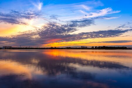 Kazanka river, Kazan, Tatarstan, Russia. Bright orange sunset in the blue sky with white clouds is reflected in the water. Romantic evening on the shore of the Russian city