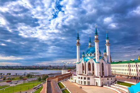 Kul Sharif Mosque in the Kazan Kremlin, Tatarstan, Russia - Jule 2015. A majestic white stone mosque with a blue roof surrounded by a red brick wall in cloudy weather with heavy rain clouds