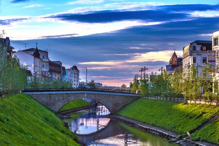 Bulak duct, Kazan, Tatarstan, Russia. A small city river, between city houses, with a grassy green slope illuminated by the setting sun