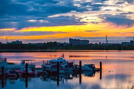 Kazanka river, Kazan, Tatarstan, Russia. Boat Rescue Station on the background of bright orange sunset in the blue sky with circling birds. Romantic evening on the shore of the Russian city