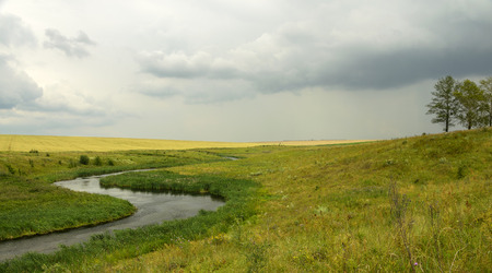 Cloudy summer landscape.River Krasivaya Mecha in Tula region, Russia.