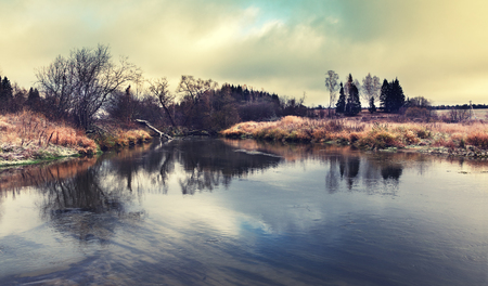 Late autumn.Cloudy landscape with small forest river.Bare trees. Stock Photo