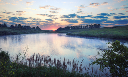 Foggy summer landscape.Twilight.Misty morning.River Krasivaya Mecha in Tula region, Russia.Sunrise.Calm.Beautiful view with rising sun.