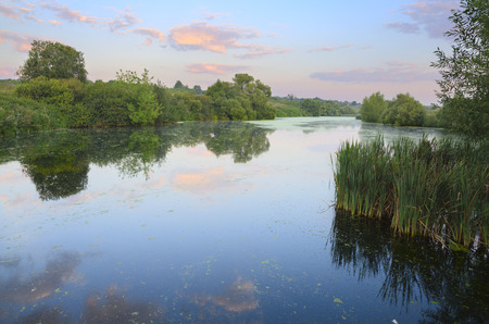 Summer morning.Serene landscape with river.Beautiful clouds in the sky.Standing water.Sunrise.River Krasivaya Mecha in Tula region, Russia.