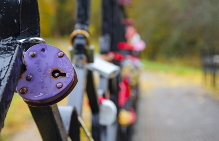 Close-up of violet heart-shaped padlock covered by water drops