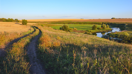 Beautiful view of the country road, river, curve, green and yellow fields illuminated by the warm light of setting sun.
