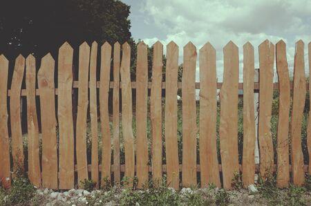 Valla de madera de jardín de tablas curvas en el patio trasero.Colores vintage.