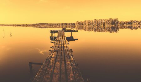 Tranquil summer morning scene with wooden bridge. Foto de archivo