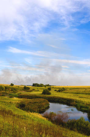 Summer rural landscape with river running through the fields and meadows. Blue sky with fluffy clouds over the land. Smoke over the land. Foto de archivo