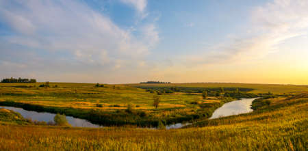 Beautiful panoramic rural nature landscape.Sunny view of small river and green meadows with trees on a background.Warm colors nature sunset scene with calm river.