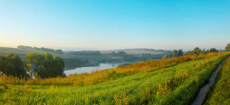 Colorful summer nature landscape.Fog over the land.Beautiful summer hazy landscape with foggy valley and green hills before the sunrise.Small calm creek runs between the meadows. Foto de archivo