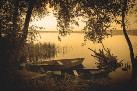Tranquil summer morning scene with boats on river bank.Vintage photo landscape made with warm sepia filter.Beautiful calm summer landscape with golden retro colors. Foto de archivo