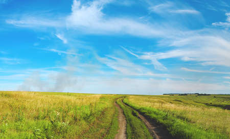 Summer rural landscape with ground road passing through the fields and meadows. Blue sky with fluffy clouds over the land. Smoke over the land.