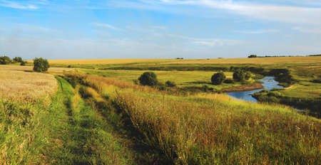 Beautiful rural road nature landscape.Sunny view of blue river and golden wheat fields with trees on a background.Warm colors nature sunset scene with calm river.