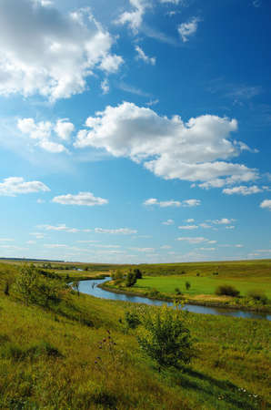 Beautiful rural summer nature landscape.Sunny view of small river and green woods.Amazing blue sky with fluffy clouds.Bright color nature sunrise scene with beautiful green hills.
