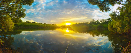 Beautiful summer sunset nature landscape. Tranquil evening scene with warm sunlight and amazing reflection of clods in sky on the water surface. Calm lake and green hills at sunset.Fishing time. Foto de archivo