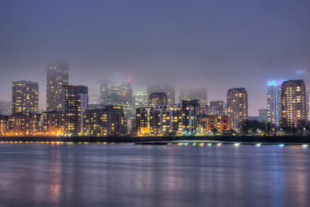 canary wharf: Night view over river Thames to foggy Canary Wharf