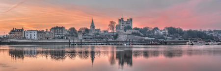 kent: Early morning picture with medieval structures, sunrise and reflection on river.