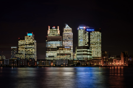 London, United Kingdom: Night panoramic view across river Thames to skyscrapers district Canary Wharf in London as seen on 26 of January, 2015. Has copy space in clear black sky.