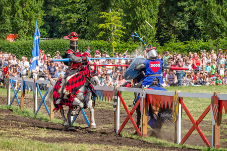 jousting: Hever, United Kingdom - July 28, 2013: Two horsemen have heavy spears contact and spectators on background at Jousting event close to Hever Castle in Kent, England Editorial