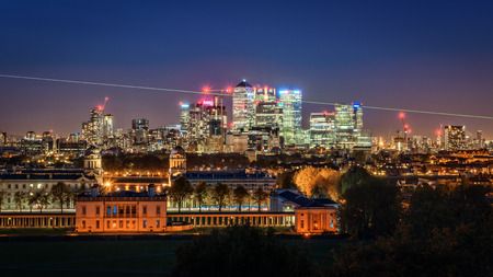 the meridian: London, UK - October 25, 2015: High visible prime meridian beam at night in London Greenwich Park near Queens House and the Naval College and with the Canary Wharf skyline with its corporate office buildings in the background. Editorial