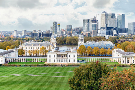 greenwich: London, UK - October 25, 2015: Autumn day in London Greenwich Park near Queens House and the Naval College and with the Canary Wharf skyline with its corporate office buildings in the background.