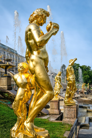 petergof: Petergof, St Petersburg, Russia - September 1, 2012: Golden statues at fountains of Grand Cascade at Grand Petergof Palace. Unidentified tourists present on picture.