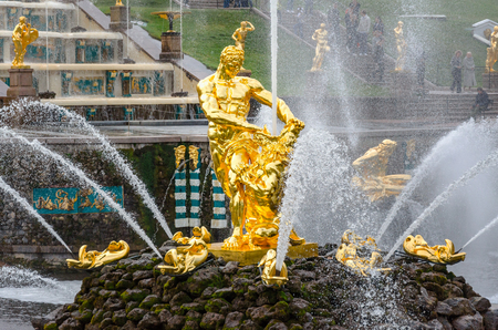 petergof: Petergof, St Petersburg, Russia - September 1, 2012: Samson  tears open the jaws of a lion is the central fountain of The Grand Cascade at Petergof Grand Palace. Unidentified tourists present on picture.