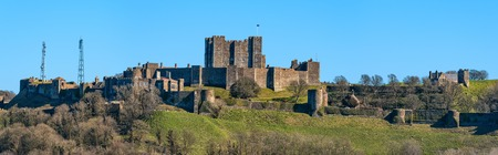 norman castle: Dover, United Kingdom - March 25, 2016: Panoramic view to Dover Castle and St Mary church  with copy space in sky. Castle was founded in the 11th century for protect the town and surrounding area for hundreds of years. Also known as Key to England. Editorial