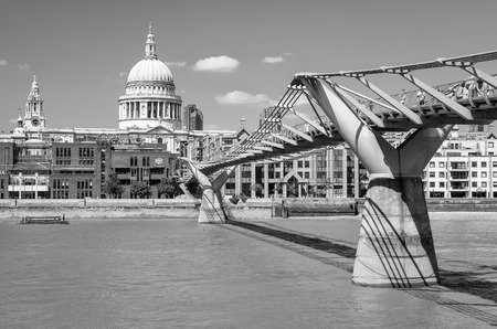 London, United Kingdom - July 19, 2013: View of Millennium footbridge across river Thames and St. Pauls cathedral on background. Unidentified people present on picture.