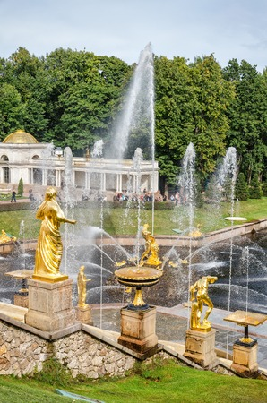 petergof: Petergof, St Petersburg, Russia - September 1, 2012: Golden statues at fountains of Grans Cascade at Grand Petergof Palace. Unidentified tourists present on picture.