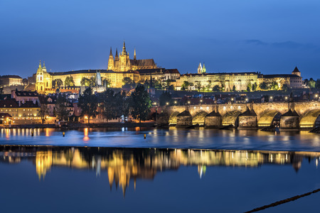 Night view over river Vltava and Charles bridge to Prague castle with copy space in clear sky