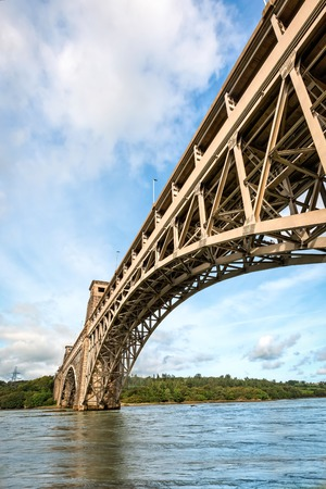 View of Britannia bridge across Menai Strait between island of Anglesey and mainland of Wales. Copy space in sky.
