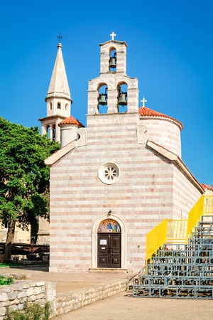 Construction of Church of Holy Trinity in Budva  was finished in 1804. It has a bell loft with three bells and a dome. Its facade is decorated with a rosette above the western door. The iconostasis of this church is the work of Greek iconographers from th Stock Photo
