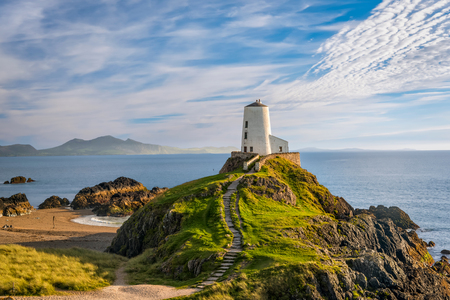 ynys: Llanddwyn island lighthouse with sea and Snowdonia mountains in background Stock Photo