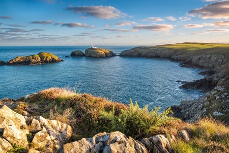 View of Strumble Head lighthouse in Wales at sunrise Stock Photo