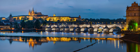 Prague, Czech Republic - May 25, 2016: Night view over river Vltava to Charles bridge and Prague castle with copy space in clear sky
