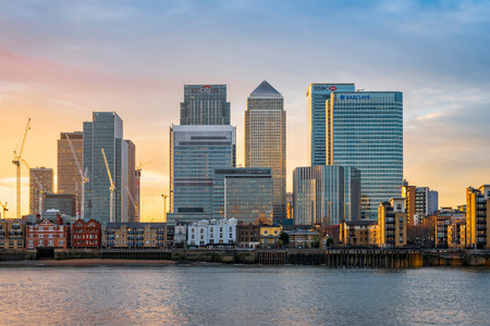 London, United Kingdom - December 22, 2016: View across river Thames to skyscrapers district Canary Wharf in London at sunset. Copy space in sky. 에디토리얼