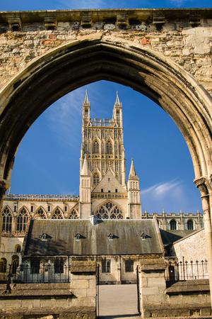 Zicht op de kathedraal van Gloucester De kerk van St. Peter en de heilige en ondeelbare drie-eenheid door overblijfselen van ziekenboegbogen
