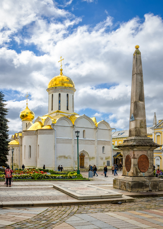 Segiyev Posad, Russia - August 30, 2012: View of obelisk and Trinity Cathedral on a cloudy summer day at Holy Trinity St. Sergius Lavra. Unidentified people present on picture.
