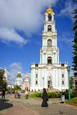 Segiyev Posad, Russia - August 30, 2012: View of bell tower at Holy Trinity St. Sergius Lavra. Unidentified people present on picture. Copy space in blue sky. Editorial